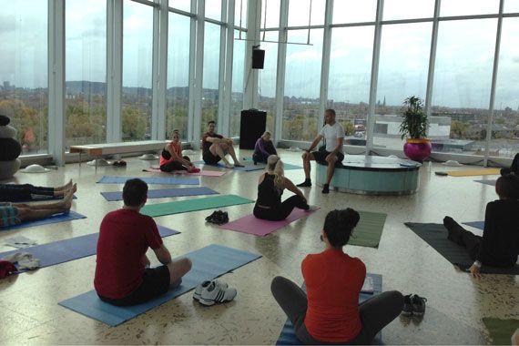 Des gens sont assis sur des tapis de yoga dans une grande salle vitrée.